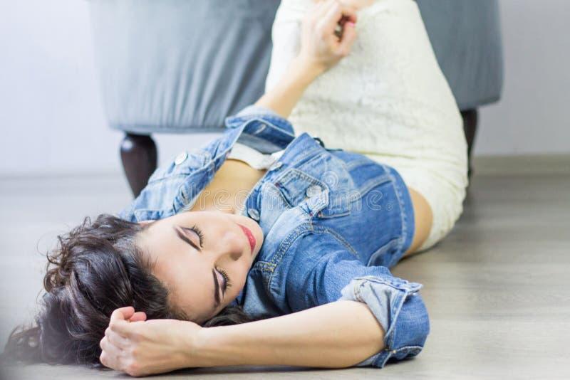 Bella giovane donna che posa nello studio che si trova sul pavimento, weari fotografia stock libera da diritti