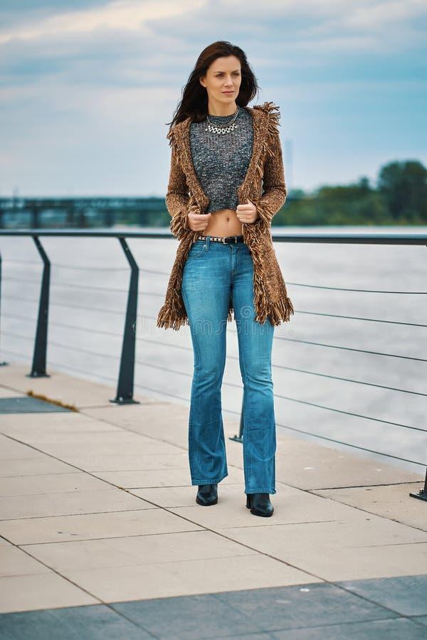Bella giovane donna che posa sulla passeggiata al fiume nella citt? immagine stock libera da diritti