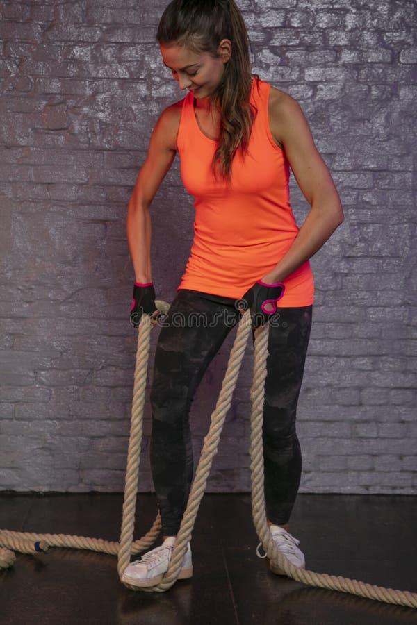 Bella giovane donna che pratica con una corda spessa immagini stock