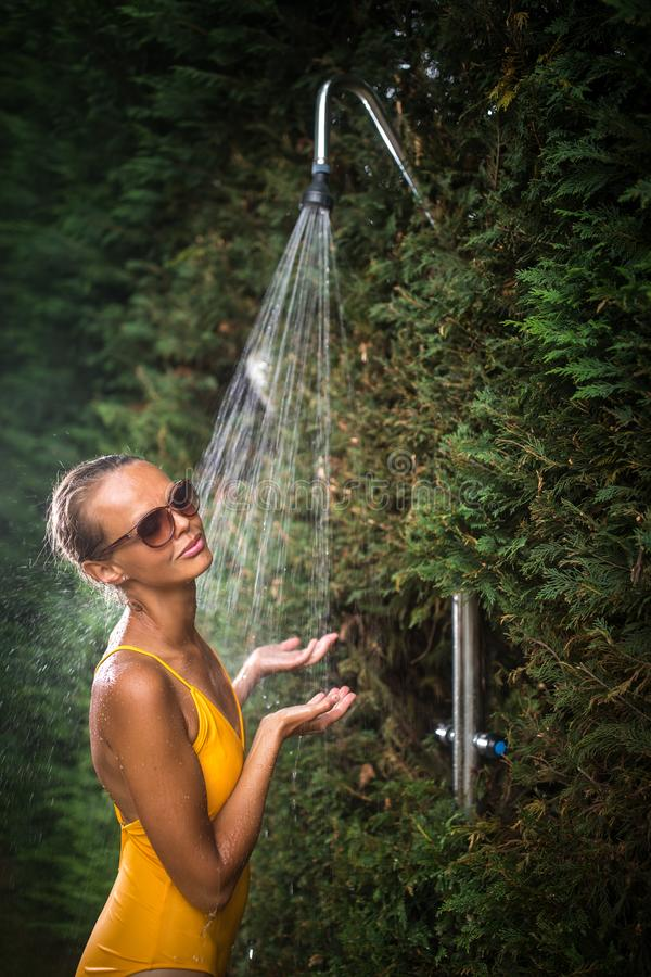 Bella giovane donna che prende una doccia all'aperto fotografie stock