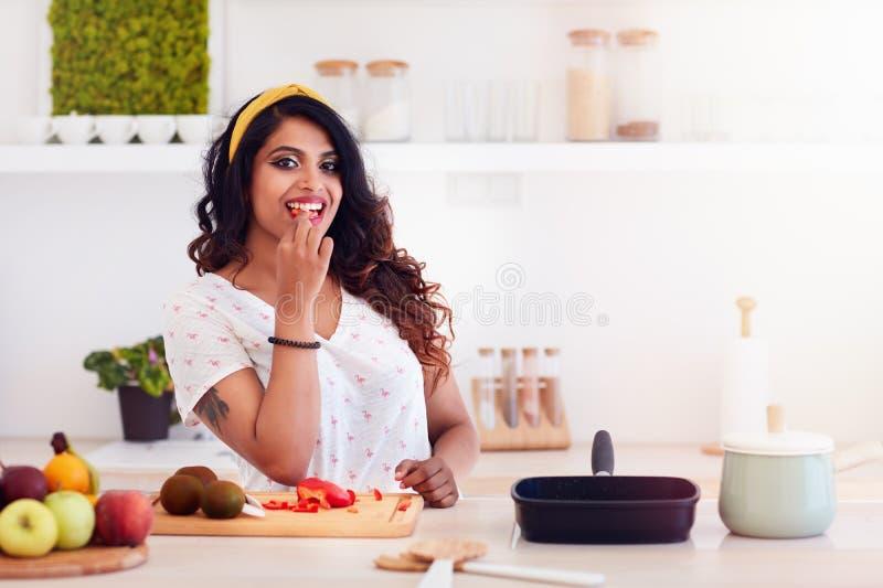Bella giovane donna che prepara pasto, mordente una verdura durante la cottura fotografie stock libere da diritti