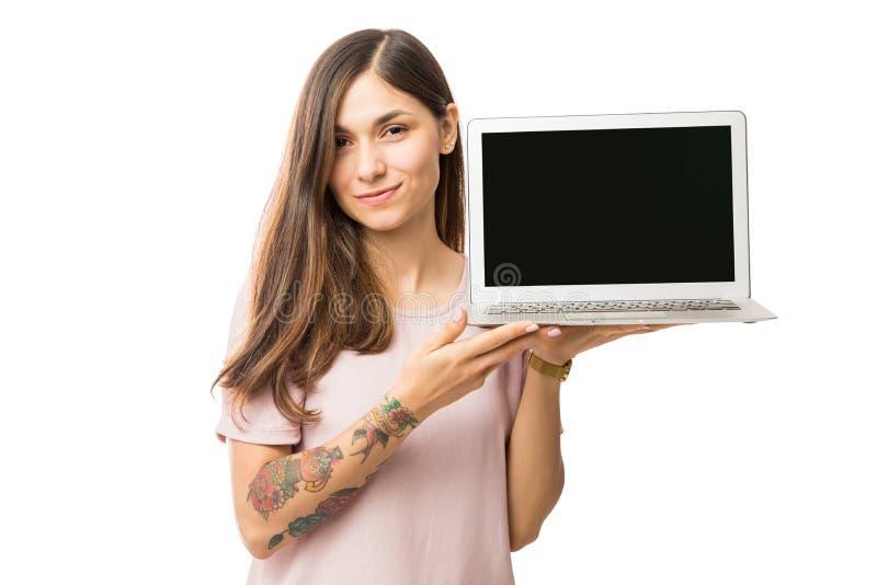 Bella giovane donna che presenta nuovo computer portatile con lo schermo nero immagini stock