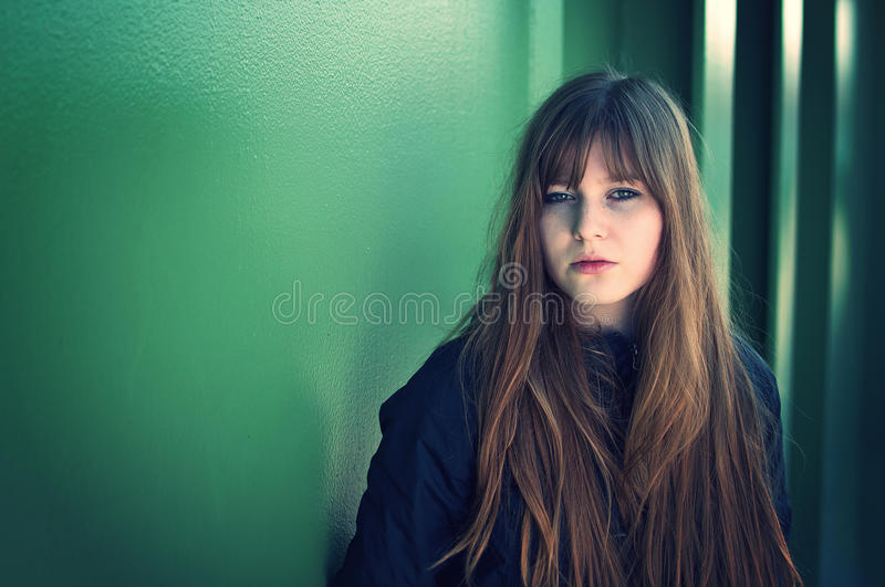 Bella giovane donna che propone dalla parete immagini stock