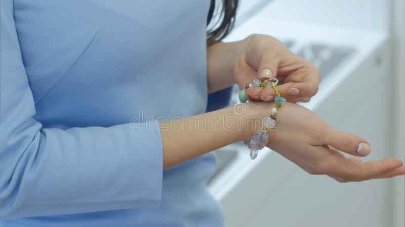 Bella giovane donna che prova sulla collana con il braccialetto progettato sulla sua mano immagine stock libera da diritti