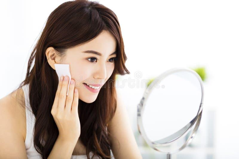 Bella giovane donna che pulisce il suo fronte con il cotone fotografia stock