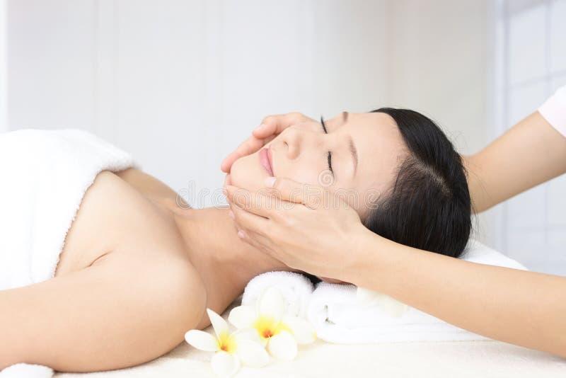 Bella giovane donna che riceve massaggio facciale immagini stock