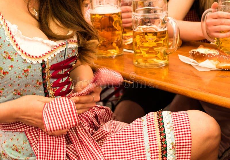 Bella giovane donna che ripara il suo Dirndl a Monaco di Baviera Oktoberfest immagine stock libera da diritti