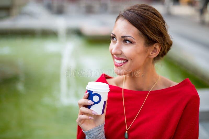 Bella giovane donna che riposa fuori ad un pozzo mentre bevendo c fotografia stock