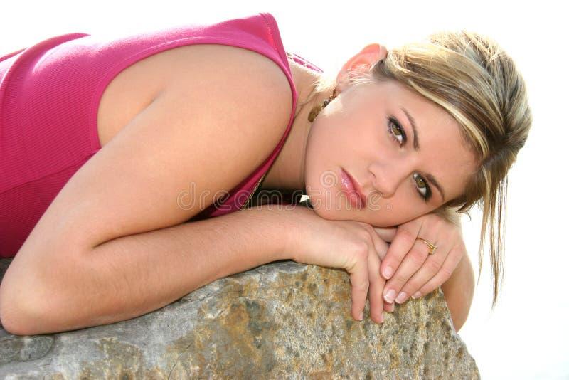 Bella giovane donna che riposa su una grande roccia fotografia stock libera da diritti