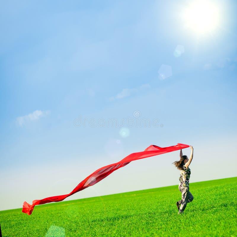 Bella giovane donna che salta su un prato verde con il tessuto colorato fotografia stock libera da diritti