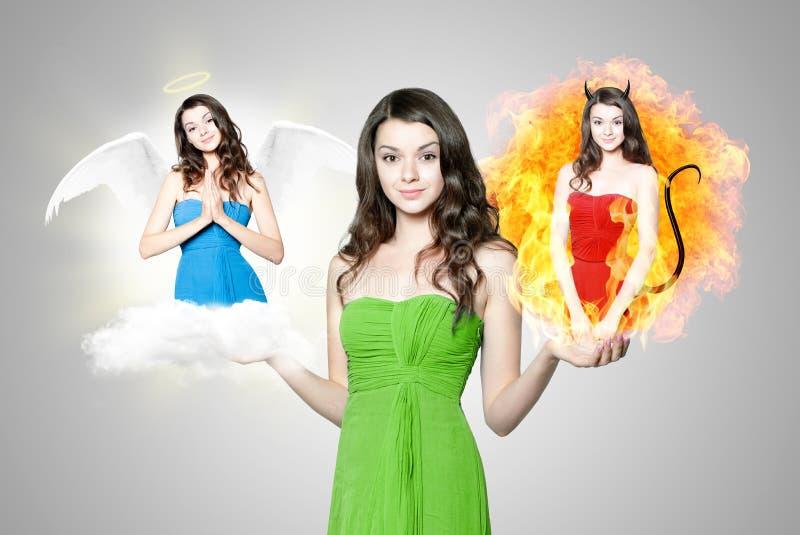 Bella giovane donna che sceglie fra l'angelo ed il diavolo immagine stock libera da diritti