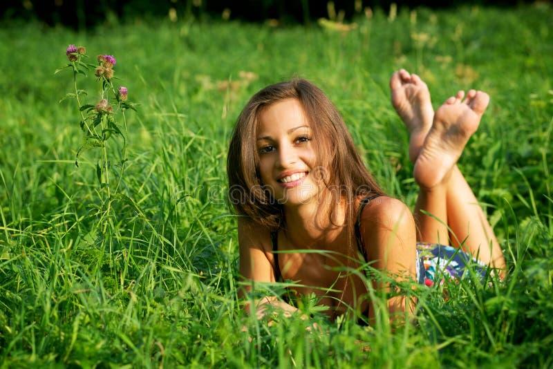 Bella giovane donna che si distende nell'erba fotografia stock libera da diritti