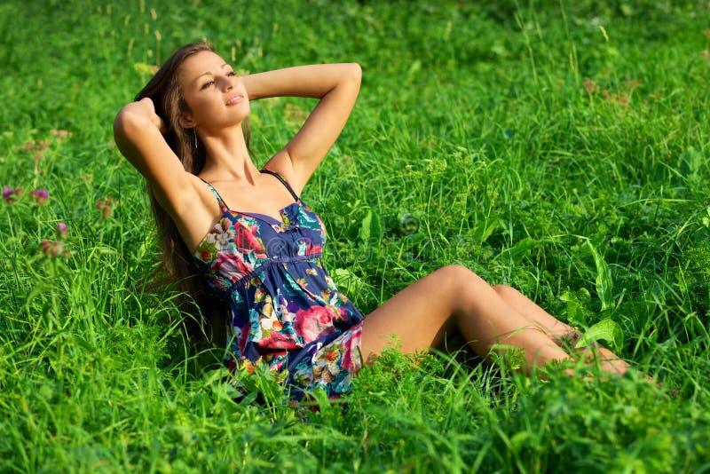Bella giovane donna che si distende nell'erba immagine stock libera da diritti