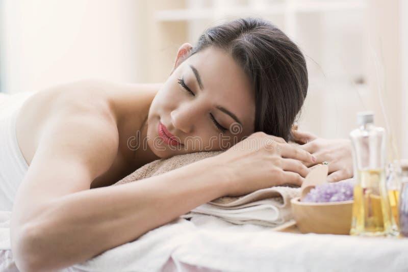 Bella giovane donna che si rilassa nel salone della stazione termale con aromatico fotografia stock