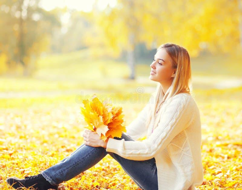 Bella giovane donna che si siede con le foglie di acero gialle in autunno soleggiato caldo fotografia stock libera da diritti