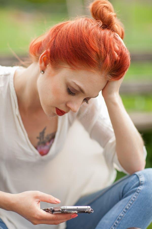 Bella giovane donna che si siede fuori, esaminando il suo telefono cellulare immagini stock