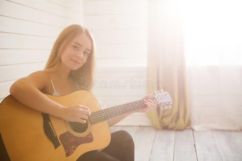 Bella giovane donna che si siede sul pavimento in abbigliamento casual a casa e che gioca chitarra immagine stock