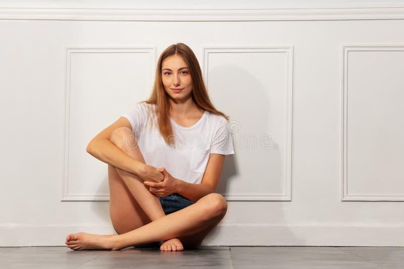 Bella giovane donna che si siede sul pavimento all'interno fotografie stock