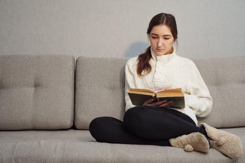 Bella giovane donna che si siede sul sofà e sul libro di lettura a casa fotografia stock