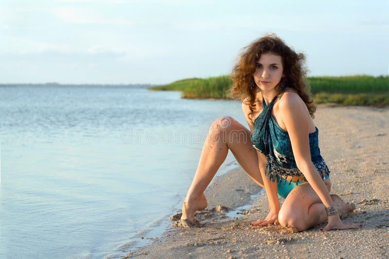 Bella giovane donna che si siede sulla baia immagine stock