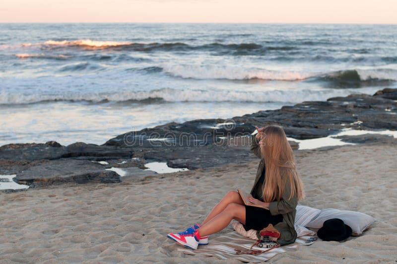 Bella giovane donna che si siede sulla spiaggia, esaminante le onde fotografia stock libera da diritti