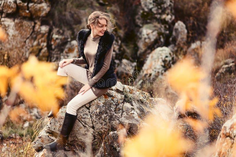 Bella giovane donna che si siede sulle rocce in autunno fotografia stock libera da diritti