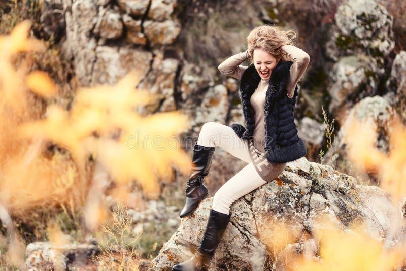 Bella giovane donna che si siede sulle rocce in autunno, viaggio immagini stock libere da diritti