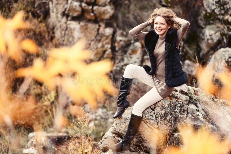 Bella giovane donna che si siede sulle rocce in autunno, viaggio fotografie stock