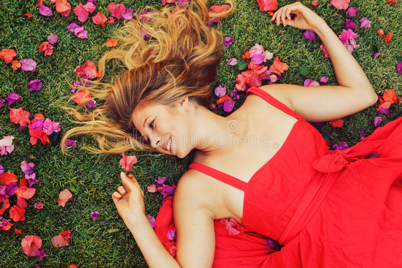 Bella giovane donna che si trova in fiori immagine stock