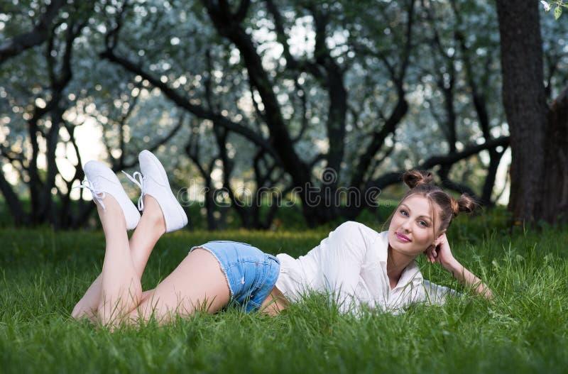 Bella giovane donna che si trova nel parco sull'erba che solleva i suoi vantaggi immagine stock libera da diritti