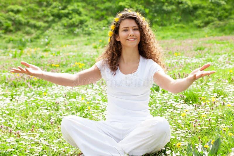 Bella giovane donna che si trova nel prato dei fiori fotografia stock libera da diritti