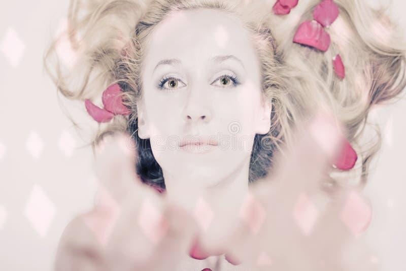 Bella giovane donna che si trova in petali di rosa fotografie stock
