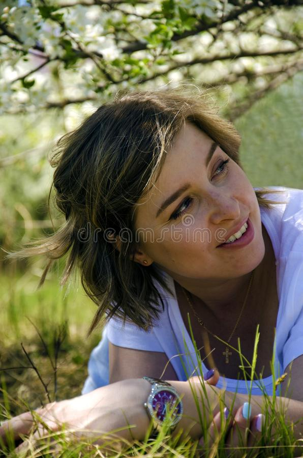 Bella giovane donna che si trova su un campo, su un'erba verde e sui fiori del dente di leone All'aperto goda della natura Ragazz immagine stock
