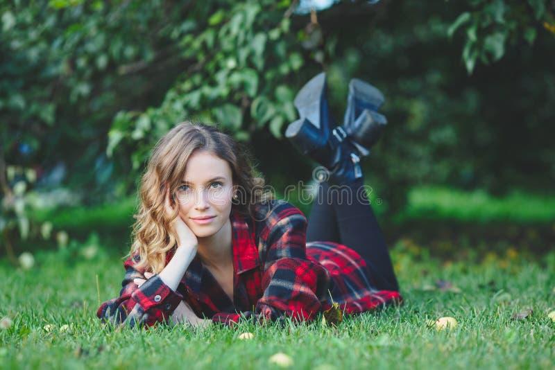 Bella giovane donna che si trova su un'erba verde immagini stock libere da diritti
