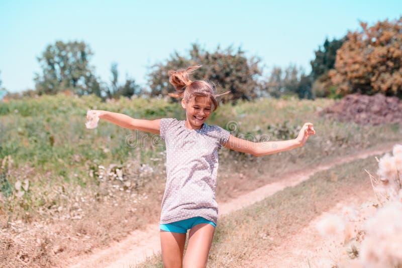 Bella giovane donna che si trova sul campo in erba verde e dente di leone di salto all'aperto Goda della natura Ragazza sorrident immagine stock