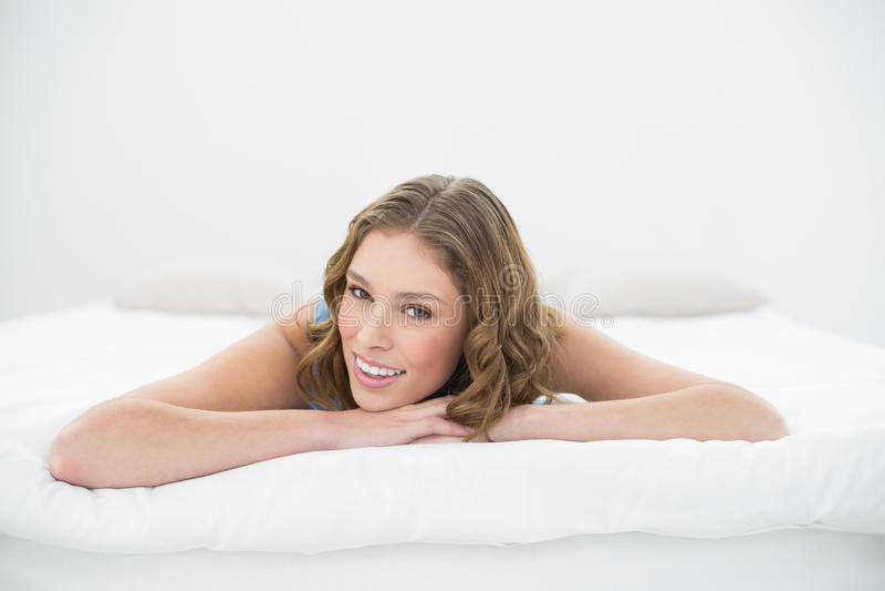 Bella giovane donna che si trova sul suo letto sulla sua pancia immagini stock libere da diritti