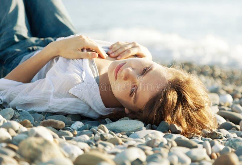 Bella giovane donna che si trova sulla spiaggia fotografie stock libere da diritti