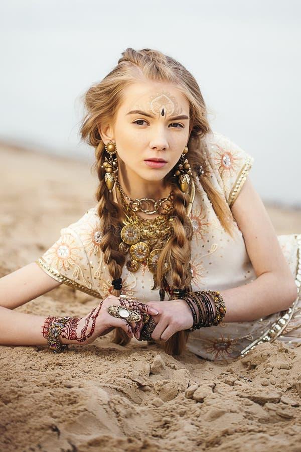 Bella giovane donna che si trova sulla spiaggia che guarda in avanti fotografia stock