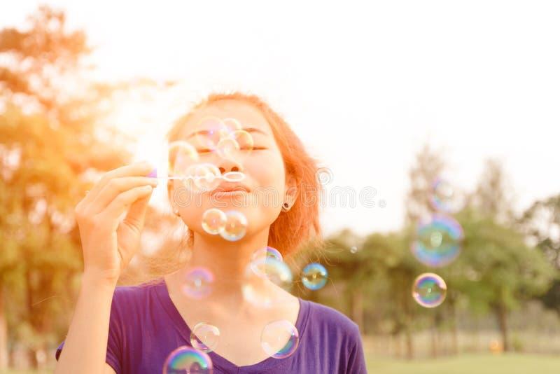Bella giovane donna che soffia felice all'aperto della bolla immagine stock libera da diritti