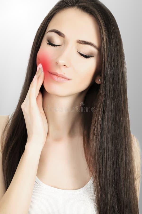 Bella giovane donna che soffre dal mal di denti, primo piano cuddles Dolore nel trattamento della mandibola di mal di denti fotografia stock libera da diritti