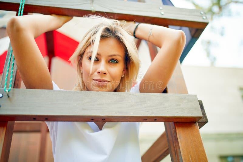 Bella giovane donna che sorride alla macchina fotografica in un parco all'aperto Ricreazione all'aperto, vita felice immagine stock libera da diritti