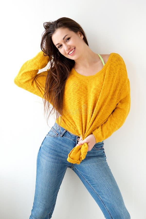 Bella giovane donna che sorride con il maglione giallo contro il fondo bianco immagini stock