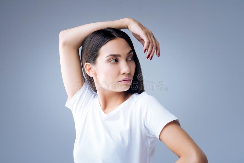Bella giovane donna che sta con il suo braccio che riposa sulla testa immagine stock