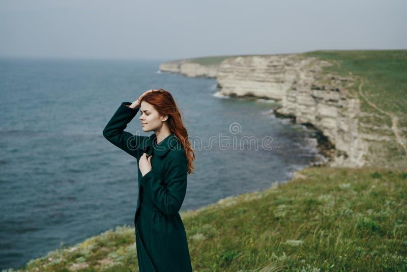 Bella giovane donna che sta su una scogliera vicino al mare immagini stock