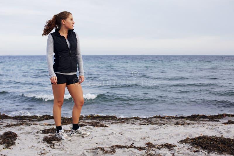 Bella giovane donna che sta sul distogliere lo sguardo della spiaggia fotografie stock