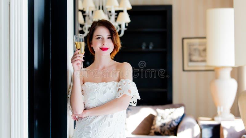 Bella giovane donna che sta vicino alla porta nel lusso leggero fotografia stock libera da diritti