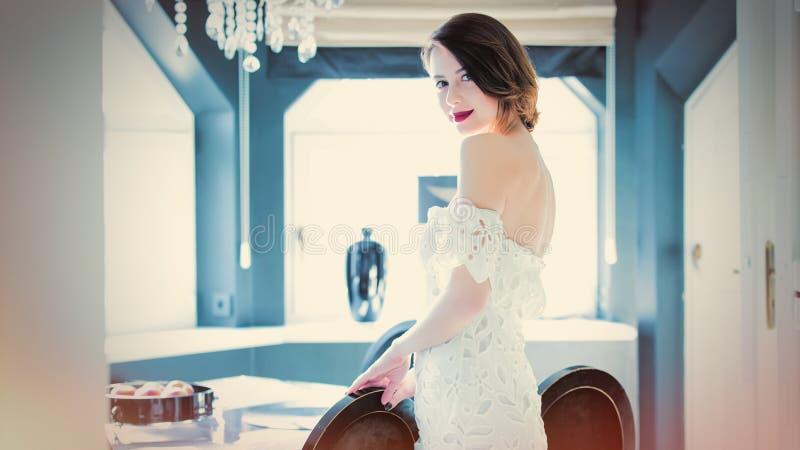 Bella giovane donna che sta vicino alla tavola nel luxur leggero immagine stock