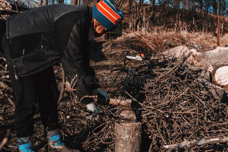 Bella giovane donna che taglia legna da ardere a pezzi con un'ascia nel villaggio durante l'inverno per riscaldare la casa immagini stock