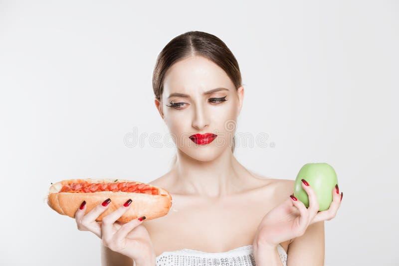 Bella giovane donna che tiene hot dog saporito e mela verde in sue mani che esaminano pasto rapido che ha dubbi per sceglierlo op immagine stock libera da diritti