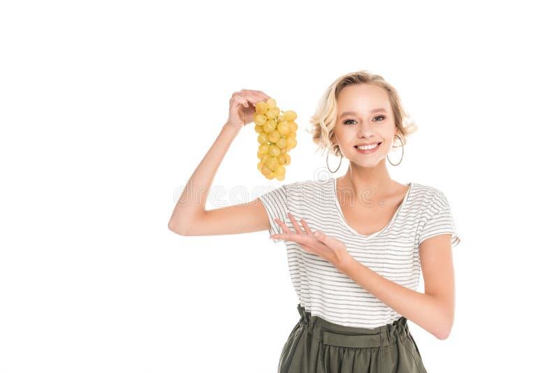 bella giovane donna che tiene mazzo di uva matura fresca e che sorride alla macchina fotografica immagine stock